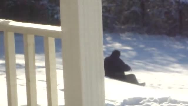 Fat man trying to sled down hill