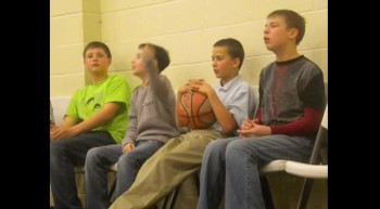 Boys doing a little cheer at a basketball game