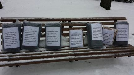 Blankets and gift cards line a bench, waiting to keep the homeless warm.